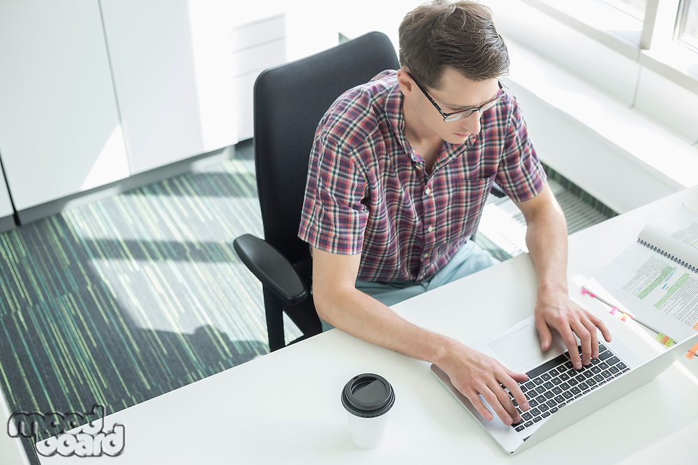 High angle view of businessman using laptop at desk in creative office
