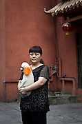 A woman holds a pet dog, with its ears dyed orange on a street in Chongqing.
