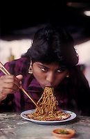 woman eating noodles in a streetfood merket