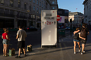 With a further 149 reported dying from Coronavirus in the last 24hrs, taking the UK death toll to 43,320, Londoners pass-by social distance advice rules on Regent Street during the Covid pandemic, on 25th June 2020, in London, England.