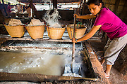 13 MARCH 2013 - BOTEN, LUANG NAMTHA, LAOS:  A woman scrapes salt out of a pan of brine at a salt factory in Boten, Laos. Salt in Boten is made by boiling briny water and collecting the salt that is left behind. The salt wells in Boten, Laos, just south of the Chinese border, have brought a measure of fame to the area for centuries. French forces asserted French dominance over the region in 1894 to control the salt trade. Some of the salt works face an uncertain future because of economic development from China. The area is being developed into a huge parking lot to accommodate truck and tourist traffic into and out of China.   PHOTO BY JACK KURTZ