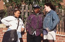 Multiracial group of teenagers standing on street corner talking,