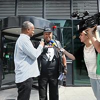 Nederland, Amsterdam , 3 juli 2014.<br /> Activist Perez Longjoy  tegen Zwarte Piet wordt voor de Rechtbank geinterviewd door media na uitspraak rechtbank in een bodemprocedure over de vraag of de vergunning voor de intocht geweigerd had moeten worden.<br /> De Gemeente Amsterdam moet het besluit over de vergunning voor de Sinterklaasintocht van vorig jaar herzien, omdat de belangen van tegenstanders van Zwarte Piet niet goed afgewogen zijn.<br /> Foto:Jean-Pierre Jans