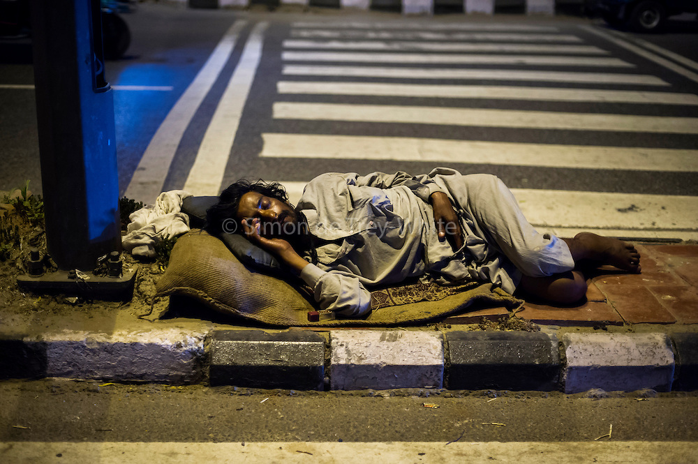 19th August 2014,New Delhi. A man sleeps on a road divider in New Delhi, India on the 19th August 2014<br /> <br /> Sleeping in the outdoors is common in Asia due to a warmer climate and the fact that personal privacy for sleep is not so culturally ingrained as it is in the West. New Delhi (where most of these images were taken) is a harsh city both in climate and environment and for those working long hours, often in hard manual labour, sleep and rest is something fallen into when exhaustion overwhelms, no matter the place or circumstance. Then there are the homeless, in Delhi figures for them from Government and NGO sources vary wildly from 25,000 to more than 10 times that. Others public sleepers may simply be travellers having a siesta along the way.<br />  <br /> <br /> PHOTOGRAPH BY AND COPYRIGHT OF SIMON DE TREY-WHITE, photographer in Delhi<br /> <br /> + 91 98103 99809<br /> email: simon@simondetreywhite.com