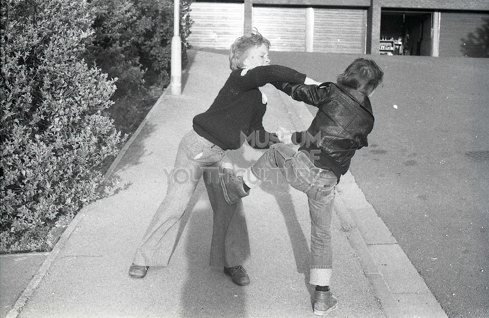 Vernon Jones in flares and Neville in turned up jeans fighting. High Wycombe, UK. 1980s.