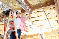 Portrait of a happy woman standing on ladder working on unfinished ceiling