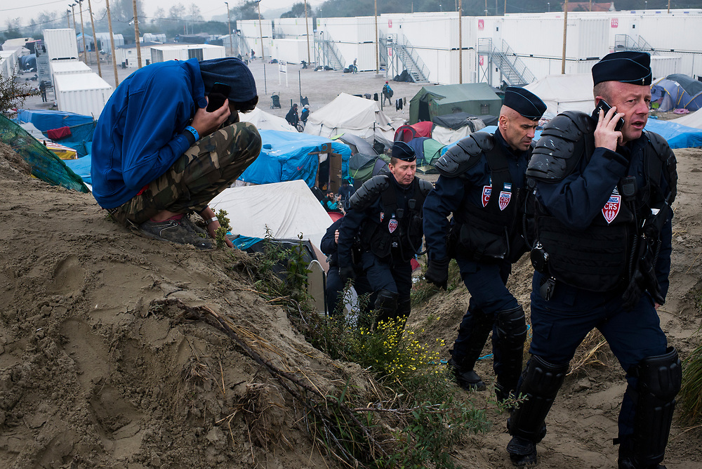A refugee makes a call as police arrive on the high ground in the middle of The Jungle refugee camp on October 26, 2016 in Calais, France.