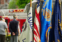 Flags rest against a granite memorial in Veteran's Square during Monday morning's Memorial Day parade.  (Karen Bobotas/for the Laconia Daily Sun)
