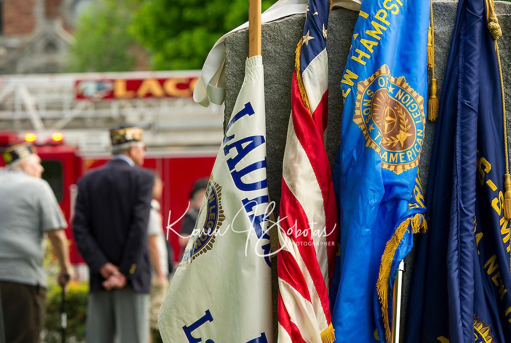 Flags rest against a granite memorial in Veteran's Square during Monday morning's Memorial Day parade.  (Karen Bobotas/for the Laconia Daily Sun)