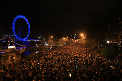© Licensed to London News Pictures. London, UK. Crowds gather in Victoria embankment to see stunning pyrotechnics at the New Year's Eve 2013 Fireworks in central London as the Big Ben's clock strikes 12 to welcome the new year 2014.