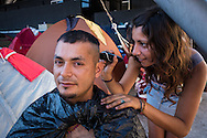 A man has his hair trimmed by a yound lady in the area of tents at the site set up for football fans who had nowhere to stay but the tents, campervans, cars and caravans that they had bought with them. The site, at the Terreirao Do Samba, Rio de Janeiro, Brazil, was arranged by the city government once they realised the number of fans in this situation was significant and rather than having them scattered about the sity they offered secure, enclosed accommodation with sanitation and water. The majority of fans at the site were Argentinian but there were also people from Chile, USA, Uruguay and Colombia. Photo by Andrew Tobin/Tobinators Ltd