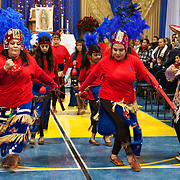 Traditional dance before mass at the Maryville Academy gym. The Feast Our Lady of Guadalupe celebration annual two-day feast celebration of Mexico's patron saint. Believers from the Chicago area gather day and night to pay homage at the shrine.  Photography by Jose More