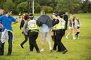 Police escort a festival goer from the site at the Glasgow Summer Sessions at Bellahouston Park on August 30, 2015 in Glasgow, Scotland. Photo by Ross Gilmore