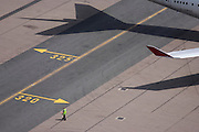 Aerial view (from control tower) of airport ramp marshal and airliner wing at London Heathrow airport.