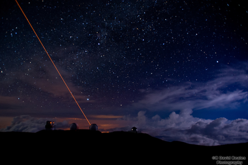 The Laser Guide Star of the Keck Observatory shines from the Summit of Mauna Kea as lightning flashes in the valley below.