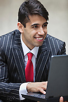 Young smiling Indian businessman using laptop
