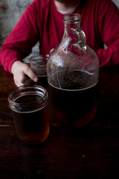 Brooklyn, NY: A man in a red shirt holds a mason jar pint glass while sitting behind a jug of beer, otherwise known as a growler in a barbecue restaurant.