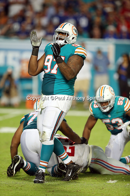 Miami Dolphins defensive tackle Jordan Phillips (97) claps his hands as he celebrates after Miami Dolphins outside linebacker Jelani Jenkins (53) stuffs a third quarter run by New York Giants running back Rashad Jennings (23) during the NFL week 14 regular season football game against the New York Giants on Monday, Dec. 14, 2015 in Miami Gardens, Fla. The Giants won the game 31-24. (©Paul Anthony Spinelli)
