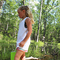 RAY VAN DUSEN/BUY AT PHOTOS.MONROECOUNTYJOURNAL.COM<br /> Sophie Hass, 8, of Hatley looks along side the path of the Northeast Mississippi Nature Trail in Amory for 662 rocks after softball practice at Concord Fields one day last week. Before going for snocones with her mom, Casey, Sophie found nine of the painted rocks at different places on the trail.