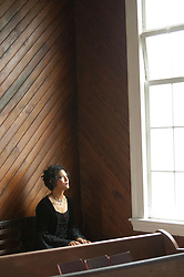 woman looking up towards the sky while sitting in church