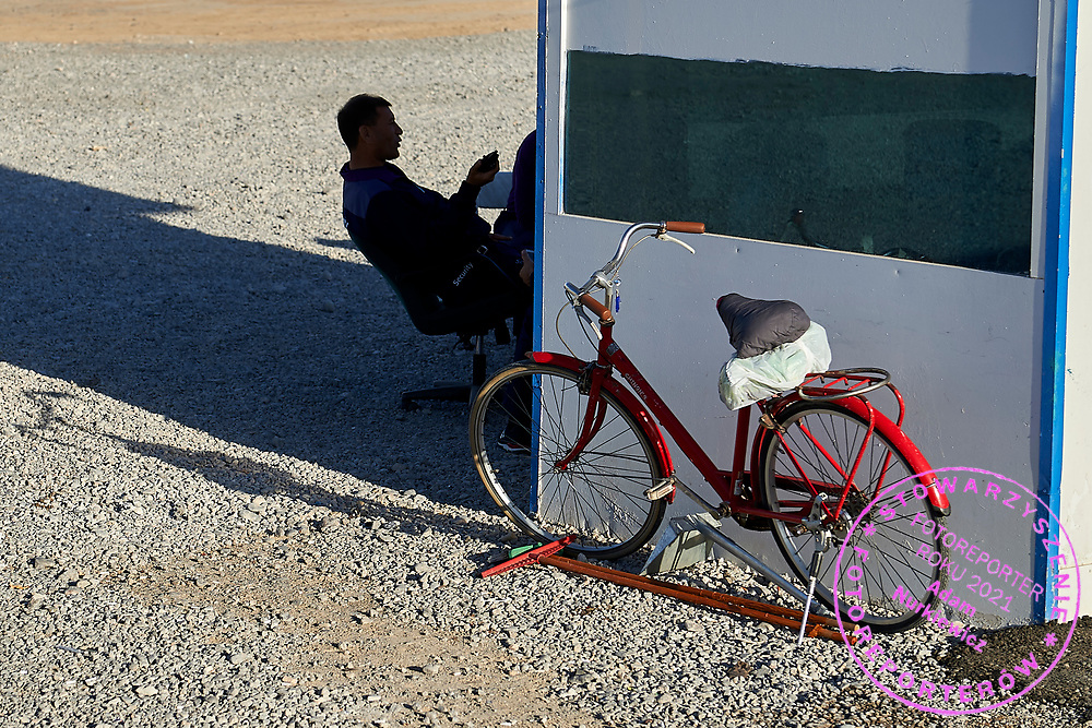 Ashgabat, Turkmenistan - 2017 September 21: Worker rests in the shadow near his red bicycle while 2017 Ashgabat 5th Asian Indoor & Martial Arts Games on September 21, 2017 in Ashgabat, Turkmenistan.<br /> <br /> Mandatory credit:<br /> Photo by © Adam Nurkiewicz<br /> <br /> Adam Nurkiewicz declares that he has no rights to the image of people at the photographs of his authorship.<br /> <br /> Picture also available in RAW (NEF) or TIFF format on special request.<br /> <br /> Any editorial, commercial or promotional use requires written permission from the author of image.