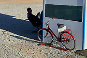 Ashgabat, Turkmenistan - 2017 September 21: Worker rests in the shadow near his red bicycle while 2017 Ashgabat 5th Asian Indoor &amp; Martial Arts Games on September 21, 2017 in Ashgabat, Turkmenistan.<br /> <br /> Mandatory credit:<br /> Photo by &copy; Adam Nurkiewicz<br /> <br /> Adam Nurkiewicz declares that he has no rights to the image of people at the photographs of his authorship.<br /> <br /> Picture also available in RAW (NEF) or TIFF format on special request.<br /> <br /> Any editorial, commercial or promotional use requires written permission from the author of image.