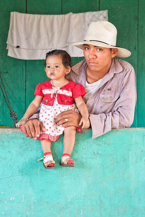 A father holding his daughter on a railing in Nicaragua.