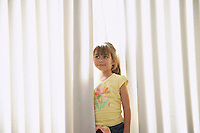 Girl (5-6) standing between blinds