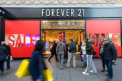 © Licensed to London News Pictures. 20/12/2014. London, UK. Christmas shoppers on London's Oxford Street on the last saturday before Christmas walk past a  storefront for Forever 21 displaying sales discounts. Photo credit : Richard Isaac/LNP
