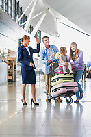 Family on holiday asking for assistance with airport staff in airport with lens flare in background