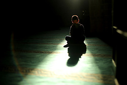 June 4, 2017 - Gaza City, The Gaza Strip, Palestine - A Palestinian boy is silhouetted against the reflection of a window in the floor of the Al-Omari mosque as he reads in a copy of the Holy Koran during prayers in the Gaza Strip,  04 June 2017. Muslims around the world celebrate the holy month of Ramadan by praying during the night time and abstaining from eating, drinking, and sexual acts daily between sunrise and sunset. Ramadan is the ninth month in the Islamic calendar and it is believed that the Koran‰??s first verse was revealed during its last 10 nights. (Credit Image: © Mahmoud Issa/Quds Net News via ZUMA Wire)