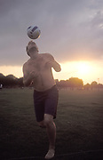 A man heading a football, in a park, at sunset, UK 2004