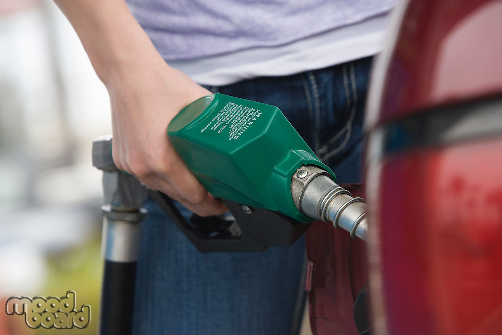 Woman by car with fuel pump, mid section