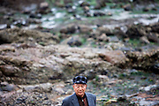 "Portrait of a visitor during low tide at Hoedong shore (Jindo Island). Jindo is the 3rd biggest island in South Korea located in the South-West end of the country and famous for the ""Mysterious Sea Route"" or ""Moses Miracle"". Every spring thousands flock to the shores of Jindo to walk the mysterious route that stretches roughly three kilometers from Hoedong to the distant island of Modo. Materializing from the rise and fall of the tides, the divide can reach as wide as forty meters."