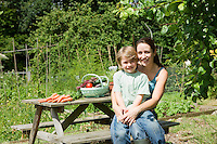Mother sitting with son in garden portrait