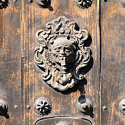 An ornate door knocker on a heavy wooden door at Iglesia de San Francisco in Antigua, Guatemala.