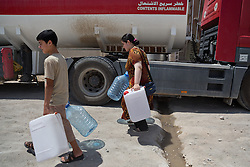 © Licensed to London News Pictures. Hamdaniyah, Iraq. 26/07/2014. Iraqi Christian refugees from Mosul haul water containers from a tanker provided by Kurdish Zeravani soldiers in Hamdaniyah, Iraq.<br /> <br /> <br /> <br /> Having taken over Mosul Iraq's second largest city in June 2014, fighter of the Islamic State (formerly known as ISIS) have systematically expelled the cities Christian population. Despite having been present in the city for more than 1600 years, Christians in the city were given just days to either convert to Islam, pay a tax for being Christian or leave; many of those that left were also robbed at gunpoint as they passed through Islamic State checkpoints.. Photo credit : Matt Cetti-Roberts/LNP