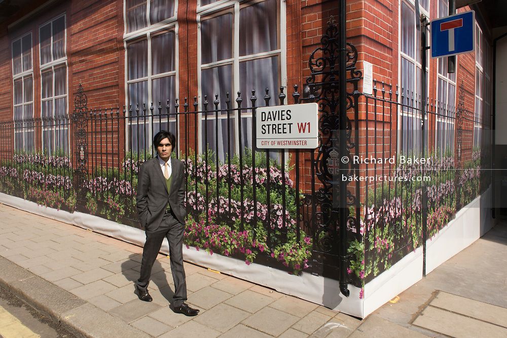 An awkward young man walks past the construction hoarding belonging to Claridges in Mayfair, Westminster.