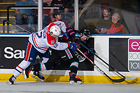KELOWNA, BC - SEPTEMBER 21:  Erik Atchison #12 of the Spokane Chiefs checks Liam Kindree #26 of the Kelowna Rockets into the boards during first period at Prospera Place on September 21, 2019 in Kelowna, Canada. (Photo by Marissa Baecker/Shoot the Breeze)