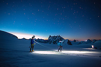 A pair of mountaineers traverses Glacier Blanche on a cold Summer night with a view on the iconic summits of Deant du Geant and Grand Jorasses.