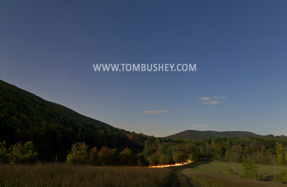 Salisbury Mills - Cars drive along Otterkill Road as the full moon shines on fields and forests by the Moodna Viaduct railroad trestle on Oct. 8, 2014.