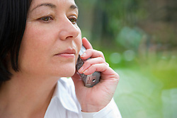 Close up of a woman talking on a cordless telephone