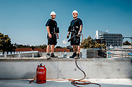 Die beiden Hamburger David Neumann und Marvin Lange sind dafür zuständig, dass in Zukunft kein Wasser durch die Dächer kommt. In der prallen Sonne ist das Flämmen mit dem Propangasbrenner eine schweißtreibende Angelegenheit.