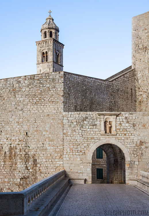 An interior wall and the Ploce Gate in the old city of Dubrovnik, Croatia. The bell tower of the Dominican Church can be seen in the background. Above the Ploce Gate stands a stone statue of St. Blaise, the City's patron.<br />