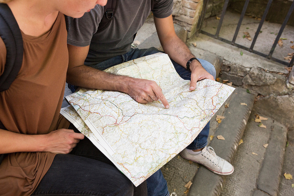 Montefioralle (Greve in Chianti), Italy - 9 September 2014: Journalist Tina Nachtmann and her travel companion Michele check a map of Tuscany in Montefioralle (Greve in Chianti), Italy, on September 9th 2014.