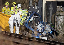 © Licensed to London News Pictures. 17/02/2018. Horsham, UK. Emergency workers in protective overalls inspect the remains of a car hit by a train near a level crossing in which  two people were killed near the village of Barns Green. Photo credit: Peter Macdiarmid/LNP