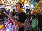 13 DECEMBER 2013 - BANGKOK, THAILAND: A vendor wearing a Santa hat sells Christmas toys in front of the Christmas lights at Central World shopping center in the Ratchaprasong area of Bangkok. Thailand is overwhelmingly Buddhist. Christmas is not a legal holiday in Thailand, but Christmas has become an important commercial holiday in Thailand, especially in Bangkok and communities with a large expatriate population.      PHOTO BY JACK KURTZ