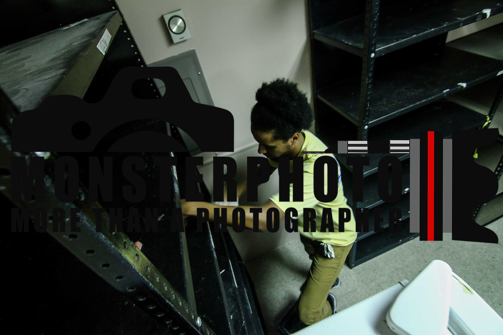 Food lion employee and volunteer Cameron Johnson of Dover wipes down a section of shelving at the Pantry of Richardson Park Community Action Center Friday, Sept 18, 2015, in Wilmington, DE.