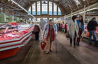 RIGA, LATVIA - CIRCA MAY 2014: Old woman walking in Riga Central Market