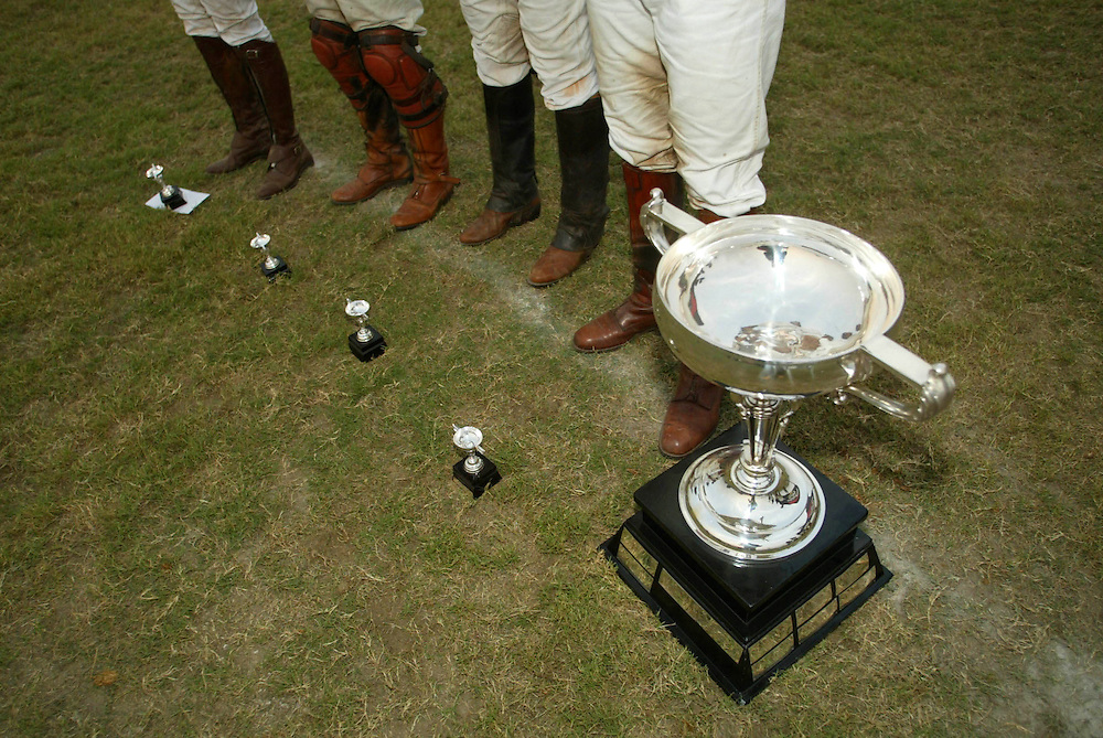 "Polo players line up with their Pizza Cup trophees, big and small, at the official award ceremony following the final match at the Jaipur Polo Ground in New Delhi, India Sunday Nov. 3, 2002.   ""Polo was a team game before,"" said Maharani Gayatri Devi, the 85-year-old queen mother of the former royal state of Jaipur, India's polo capital.  A 21st-century magnate may be a mediocre player, but he can ride with the best by hiring professionals ""assassins,"" polo's old guard calls them"